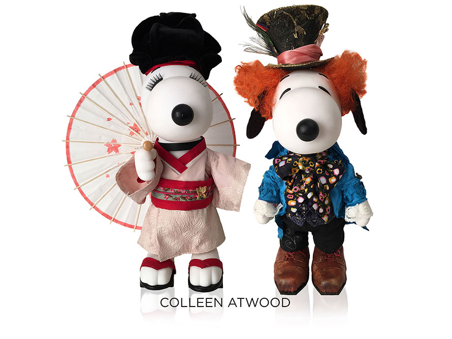 Two black and white dog statues in front of a white background. The dog on the left is wearing a Japanese kimono and holding an umbrella and the dog on the right is wearing a blue tuxedo, an orange wig and a top hat.