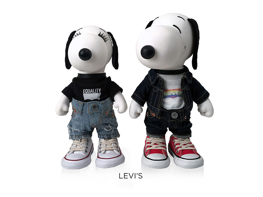 Two black and white, stuffed toy dogs standing in front of a white background. The dog on the left is wearing a black t-shirt and blue jeans and the dog on the right is wearing dark jeans and a jean jacket.