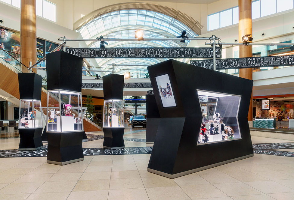Several glass displays showcasing figurines inside a mall.