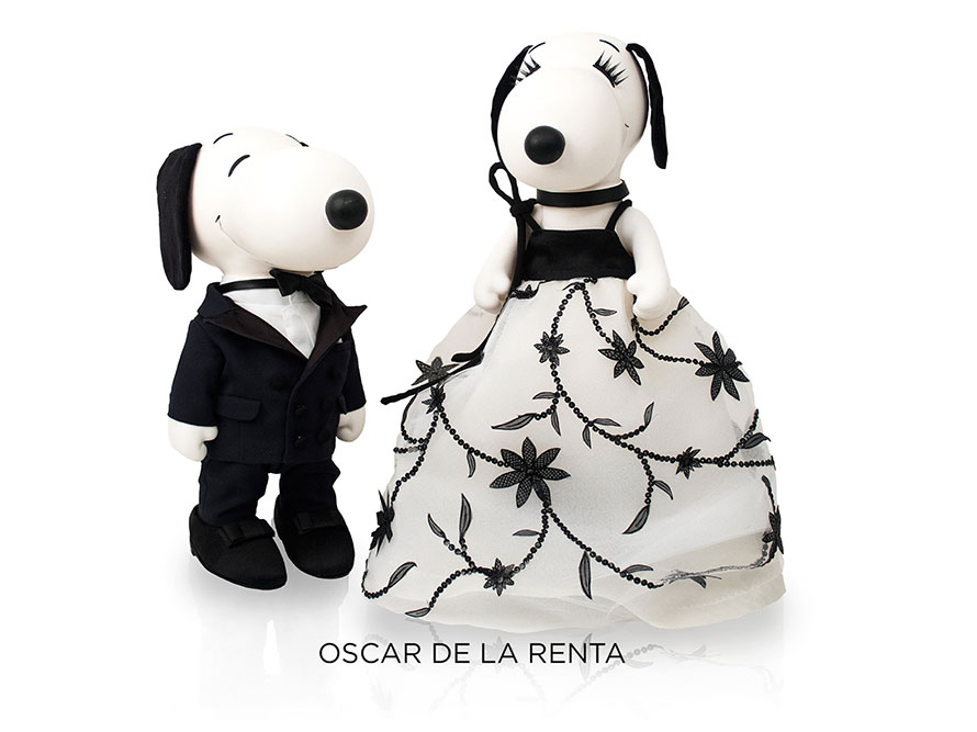 Two black and white, stuffed toy dogs in front of a white background. One is wearing a green dress and a vail and the other one is wearing a black and beige tuxedo.