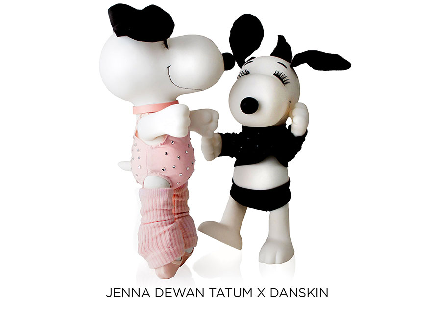 Two black and white dog statues in front of a white background. The dog on the left is standing on it's tippy toes, wearing a pink suit and ballet shoes.