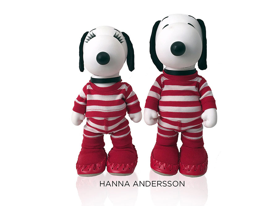 Two black and white, stuffed toy dogs standing in front of a white background wearing  red and white striped outfits.