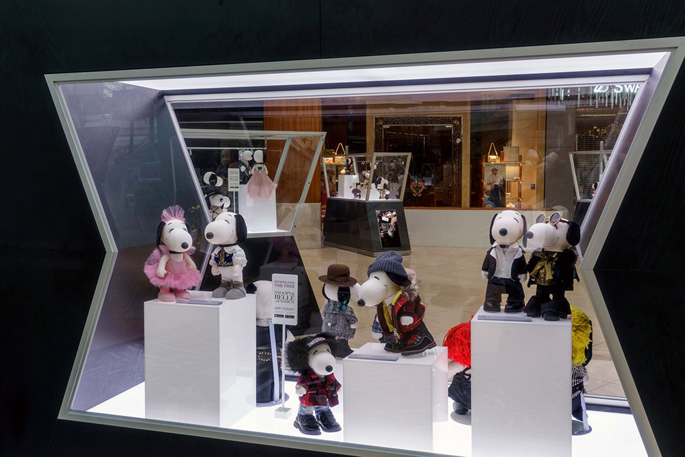 A glass display of black and white dog statues wearing various costumes.