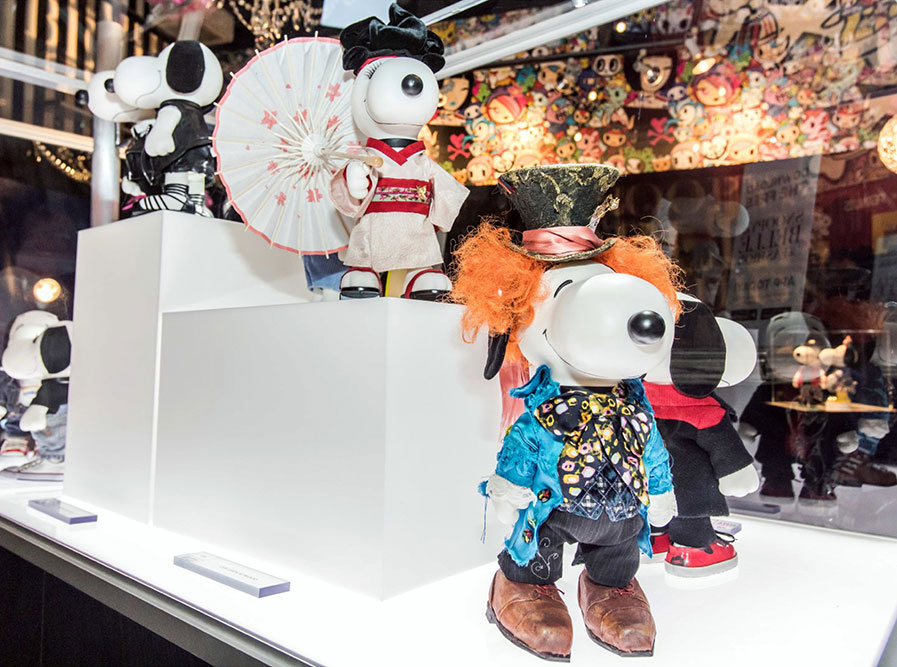A close-up view of a black and white dog figurine inside a glass display. He is wearing an orange wig, a top hat and a blue and black suit.