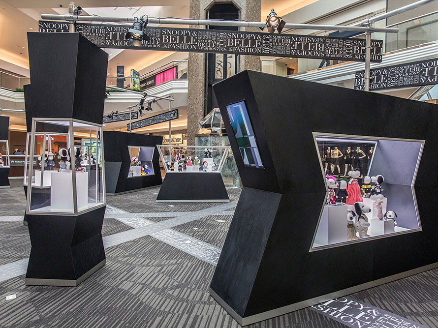 An indoor space with several black and glass displays featuring black and white dog statues.