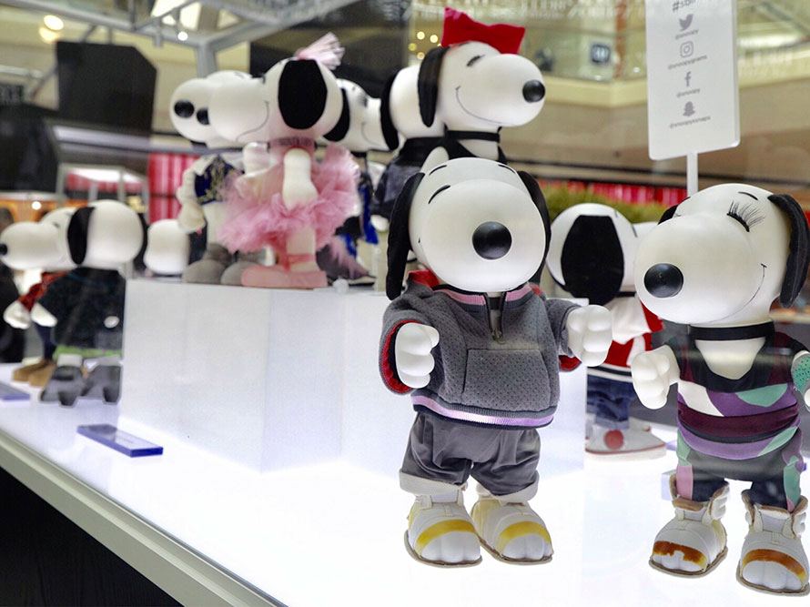 A close-up view inside a glass display of black and white dog statues wearing various outfits.