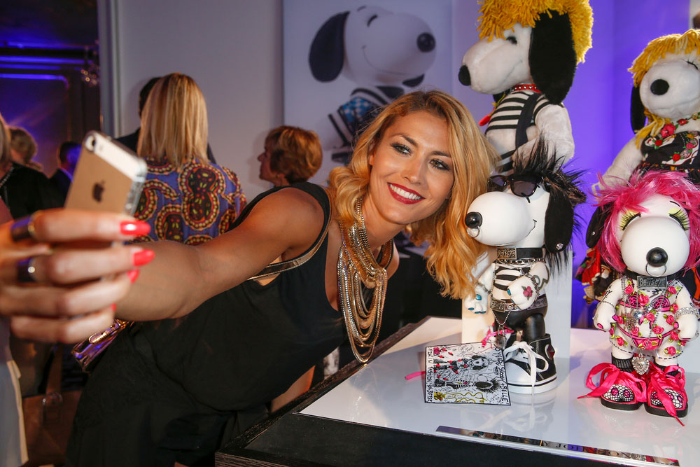 A blonde woman, wearing a black dress, leaning over taking a selfie with a small black and white dog statue wearing a costume.