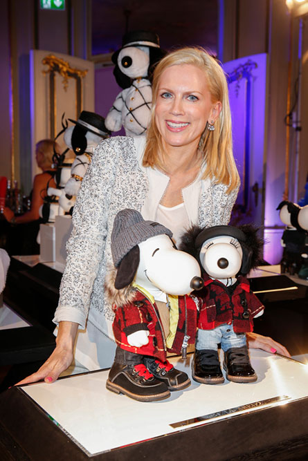 A women with short blonde hair smiling and leaning over towards a display of two black and white dog statues.