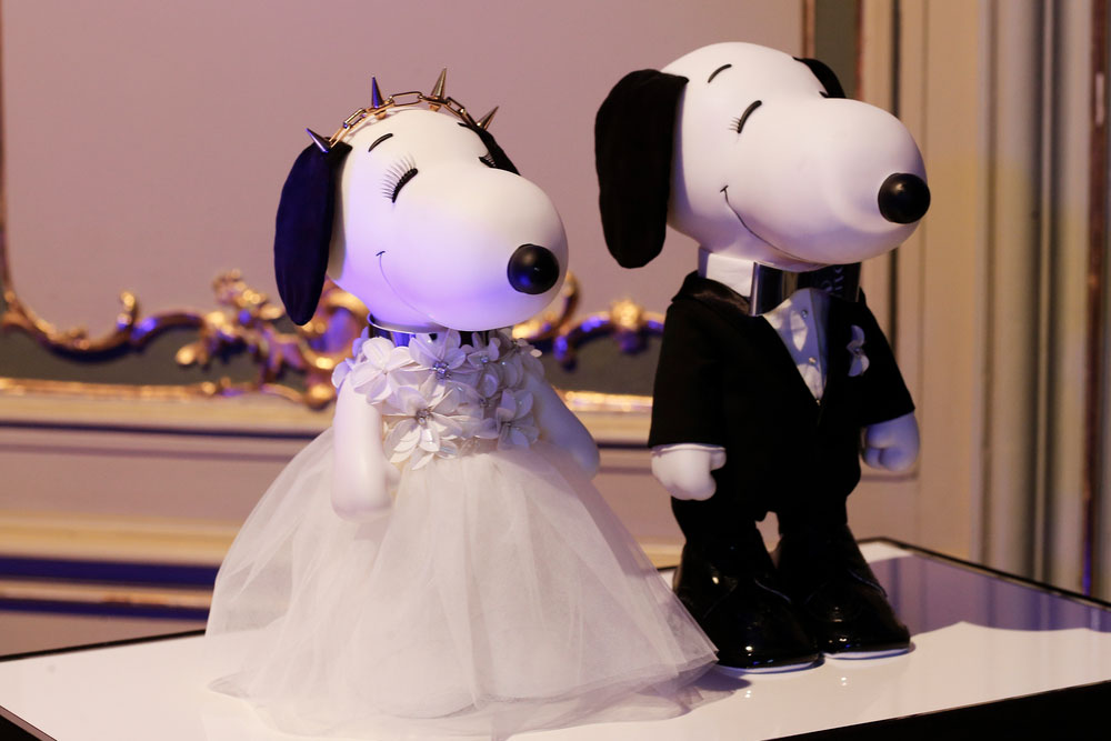 A close-up of two black and white dog statues on display. One is wearing a white gown and the other one a black suit.