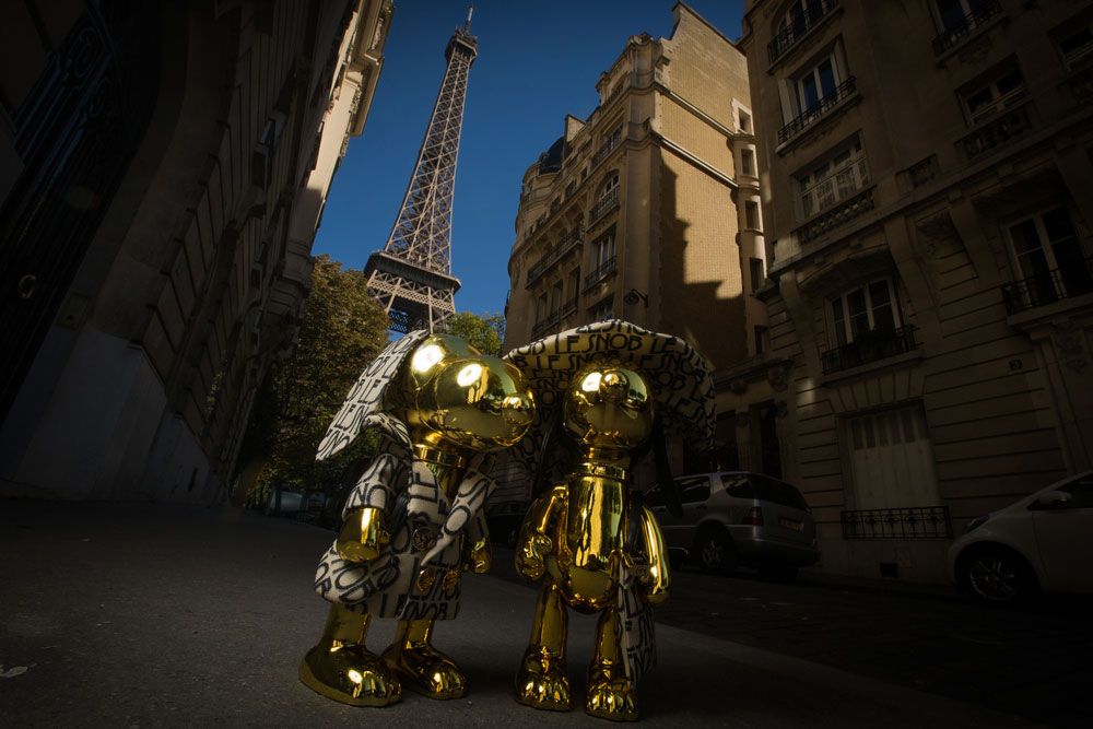 Two gold, dog statues in the middle of a residential street in Paris with the Eiffel tower in the background.