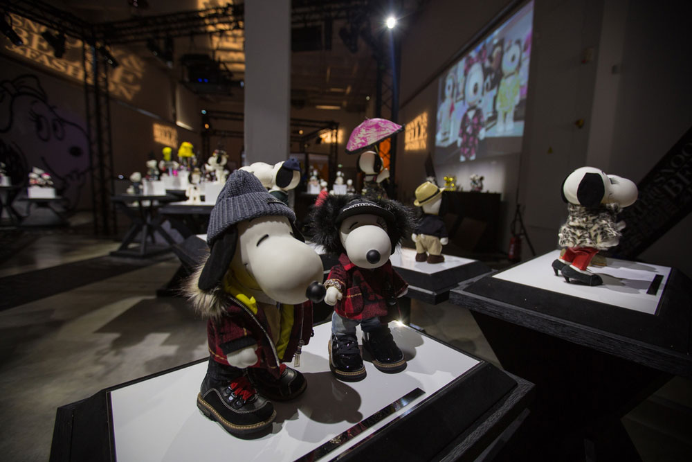 Black and white dog statues, wearing various costumes, on display in a dim, indoor space.