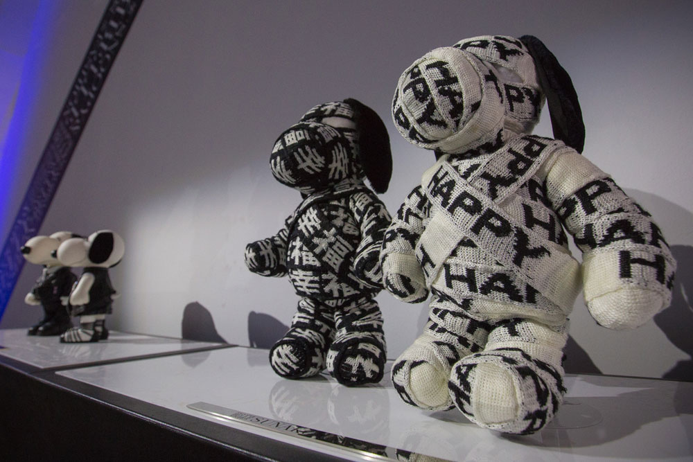 A low angle view of two dog statues on display, wrapped up in black and white fabric.