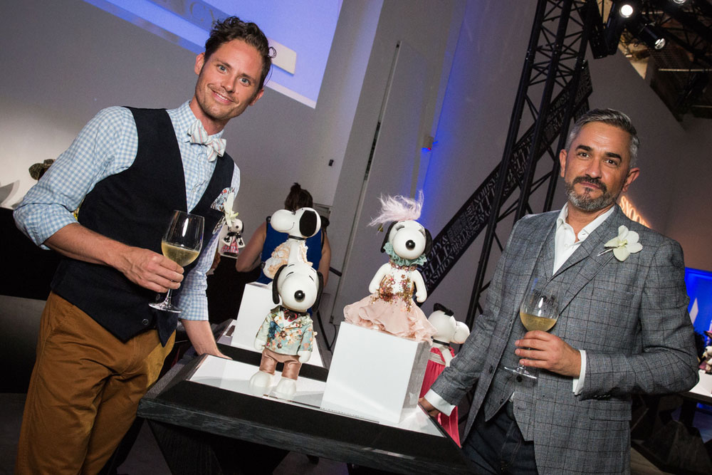 Two men, wearing semi-formal attire, standing next to a display of small black and white dog statues wearing costumes.