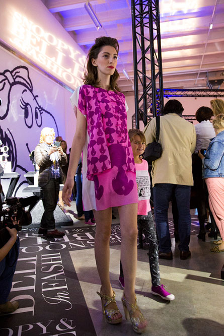 A tall, lean woman modelling a short pink dress at an indoor event space. There are people in the background.