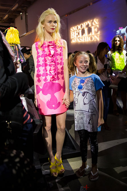 A tall, blonde model, wearing a short pink dress is holding a young girls hand. They are modelling clothes at an indoor event.
