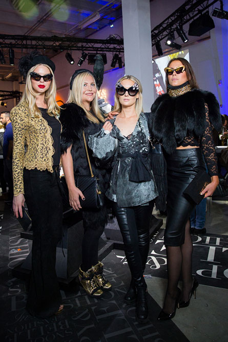 Four women, in semi formal attire, posing for a photo at an event. Three of the women are wearing unique sunglasses.