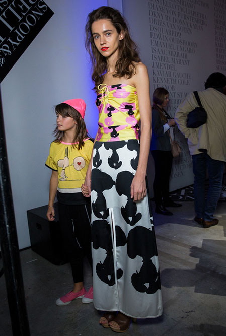 A tall, lean woman and a young girl modelling clothes at an indoor event.