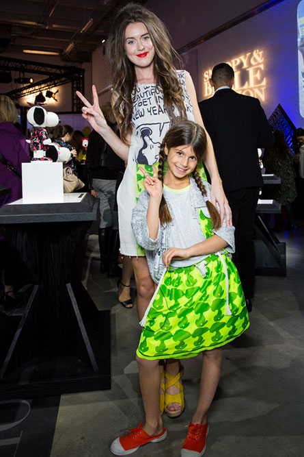 A tall, lean woman and a young girl modelling clothes at an event. They are posing for a photo and making a peace sign with their hand.
