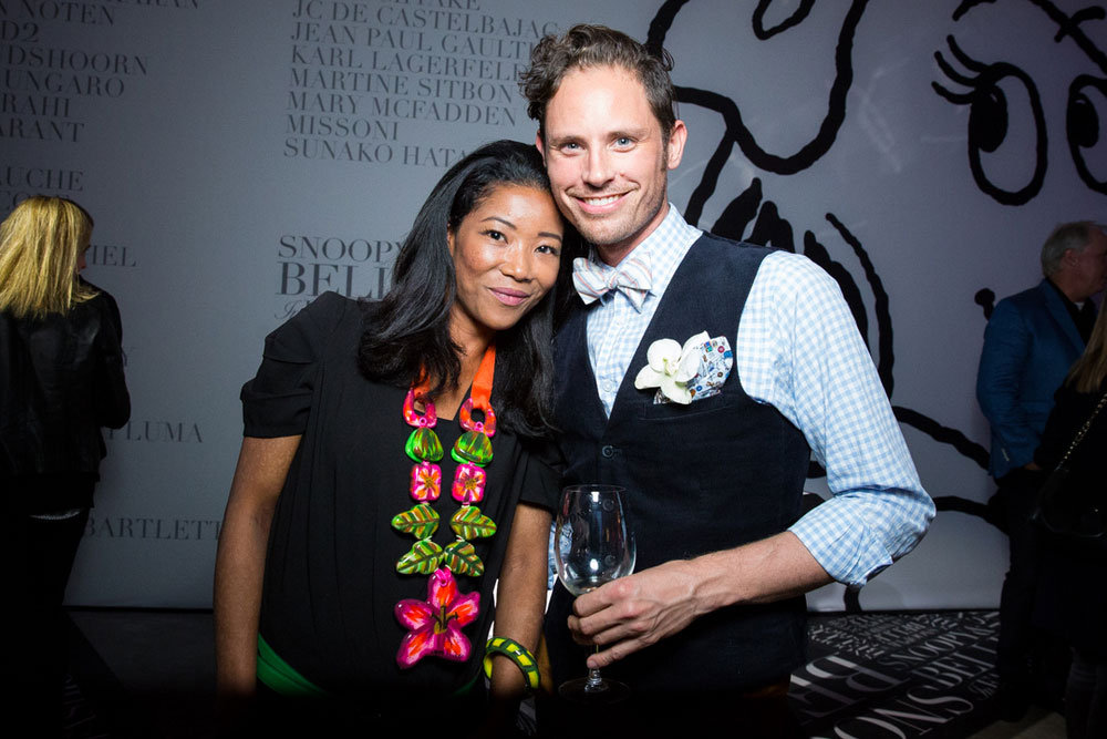 A man and  woman, dressed in semi formal attire, posing for a photo at an event. The man is holding a wine glass in his hand.