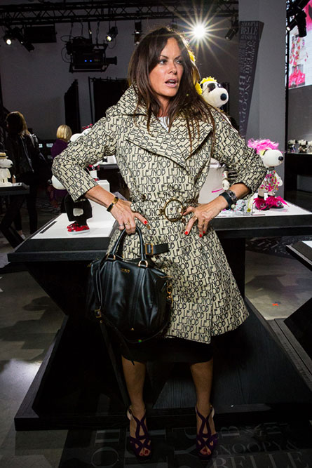 A brunette woman striking a pose at an indoor space. She is wearing a beige and black coat, a black purse and is has her hands on her hips.
