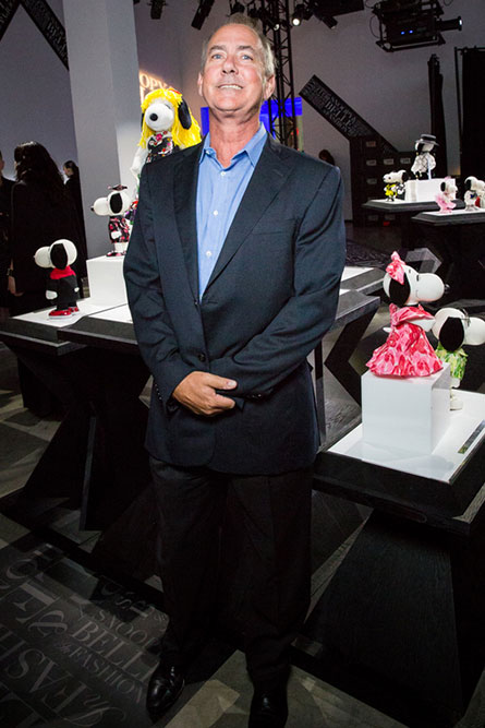 A middle aged man with grey hair, wearing a blue suit, posing for a photo at an indoor event. He is standing in front of a display of black and white dog statues.