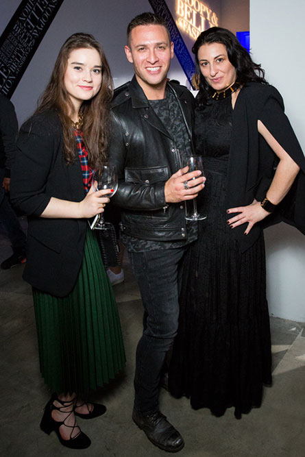 Two women and one man, wearing black, semi-formal clothes, posing for a phot at an event.
