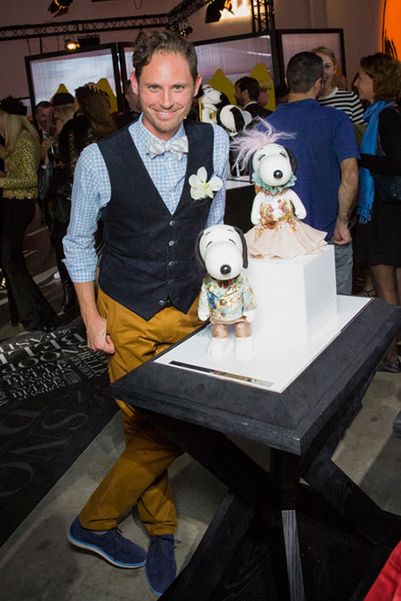 A man wearing yellow pants, a blue shirt and a blue vest posing for a photo in front of a display of black and white dog statues.