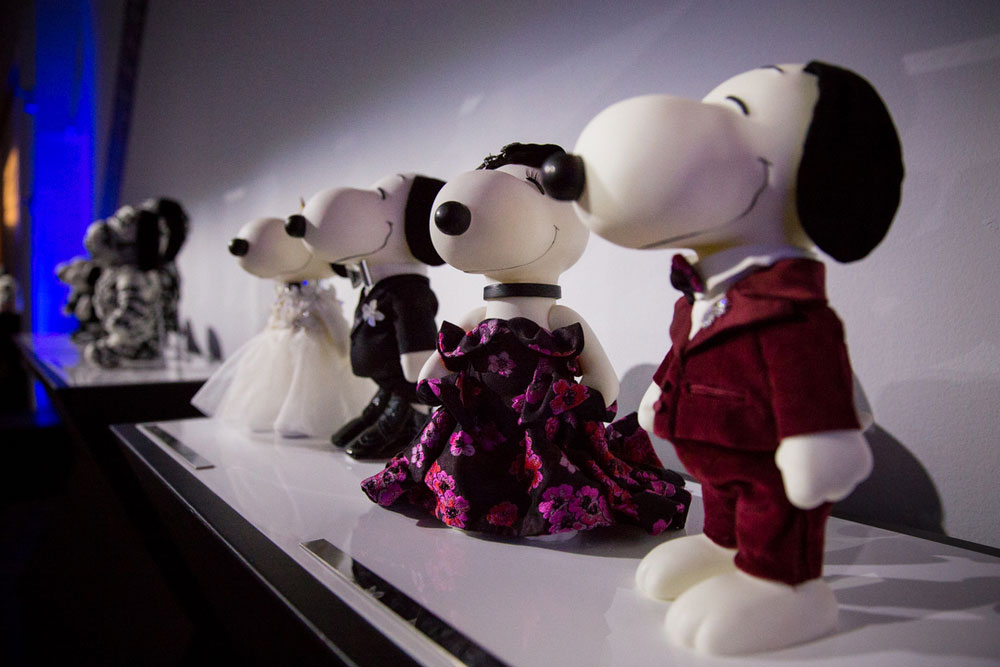 Four black and white dog statues on display in an darkly lit room.