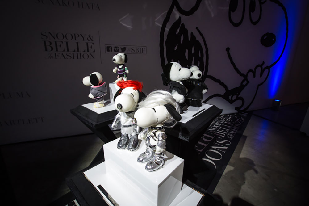 Black and white dog statues, wearing various costumes, on display in a darkly lit room.
