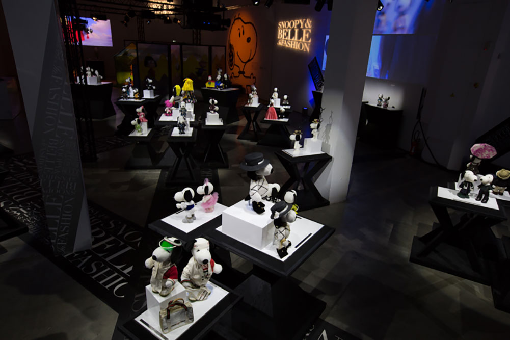 An darkly lit,  indoor space displaying black and white dog statues wearing various costumes.