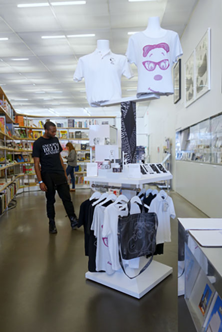 A man shopping in a retail store, looking at a display of white t-shirts and bags.