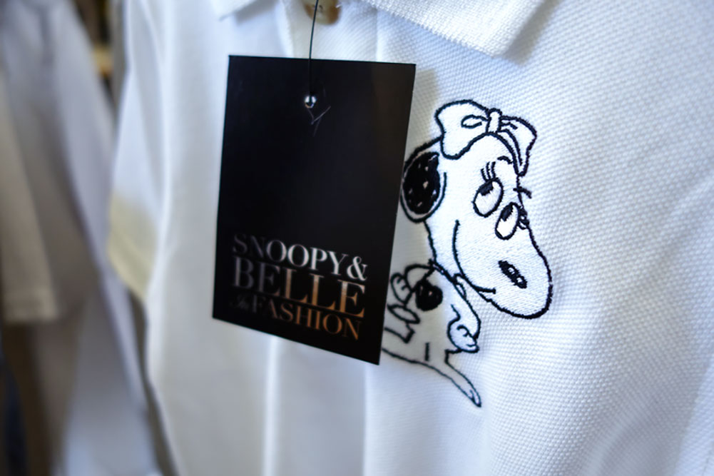 A close up of a black price tag hanging off a white shirt with a small illustration of a dog.