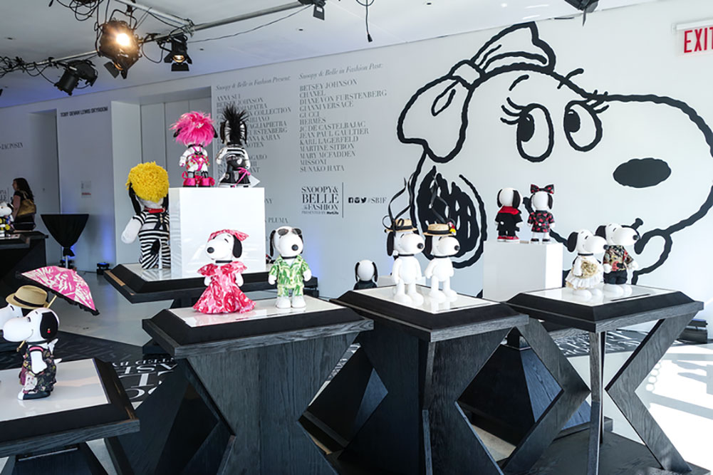 A bright indoor space with black stands displaying small black and white dog statues wearing designer costumes.