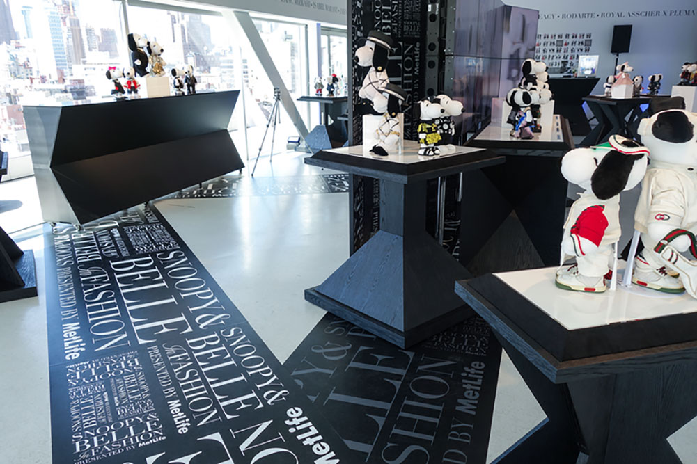 A bright indoor space displaying small black and white dog statues wearing designer costumes.