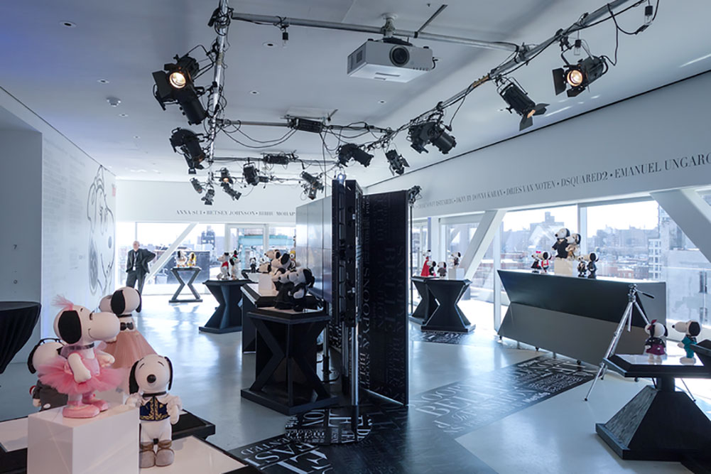 A bright indoor space with white walls and floor to ceiling windows and a bunch of tables displaying small black and white dog statues.