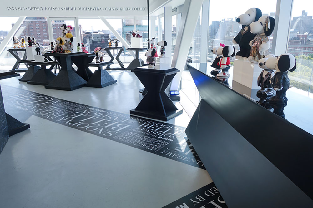A bright indoor space with large windows and a bunch of tables displaying small, black and white dog statues wearing designer costumes.