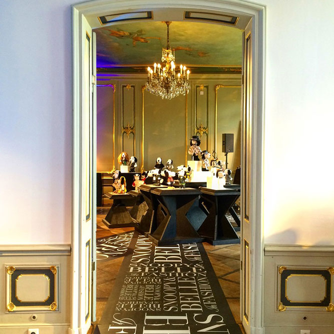 An antique door frame and a display of black and white dog statues in the distance in a separate room.