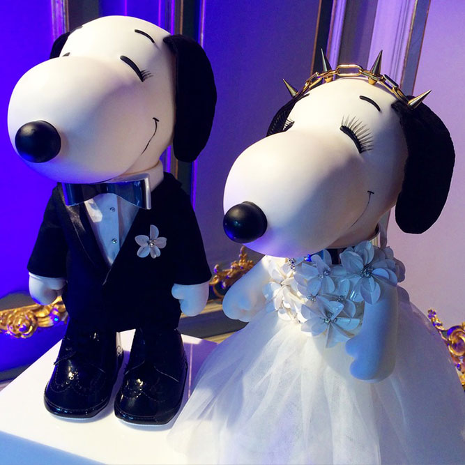 Two black and white dog statues. One is wearing a black suit and the other one a wedding dress.