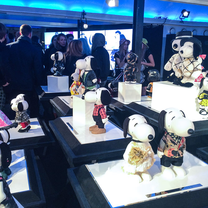 People mingling in an indoor space with several displays of black and white dog statues wearing designer costumes.
