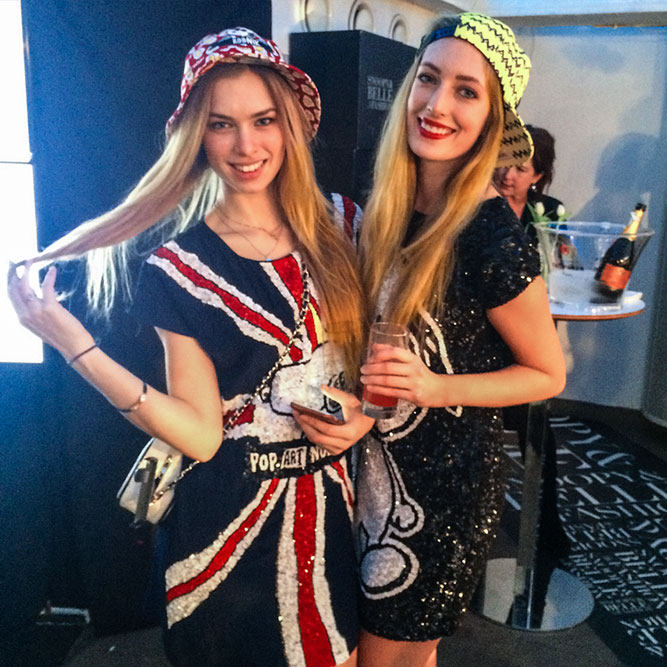 Two blonde women posing for a photo at an indoor event. They are wearing fun and colourful outfits.
