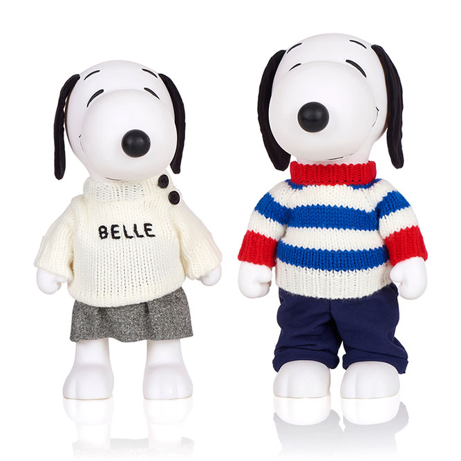 Two black and white dog statues in front of a white background. The dog on the left is wearing a white sweater and a grey skirt. The dog on the right is wearing blue jeans and a black and white sweater with red details.