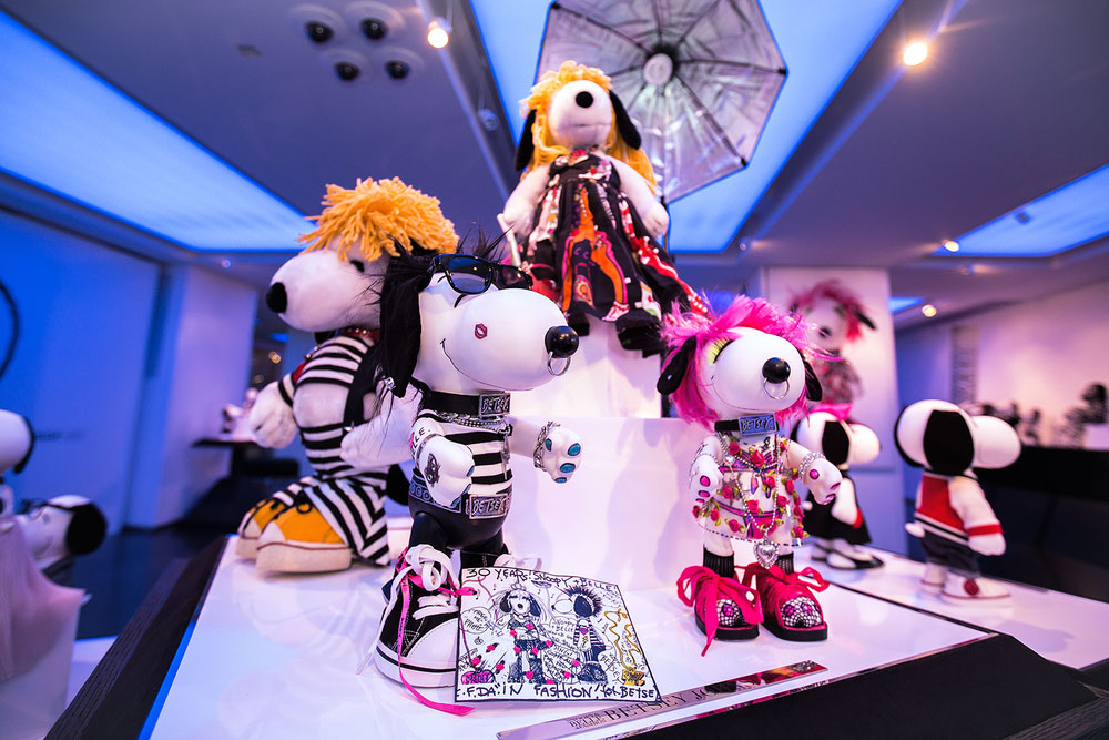 A close-up of black and white dog statues on display, wearing bright and colourful costumes.