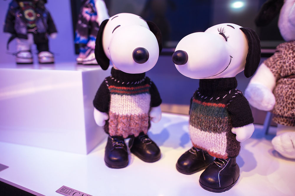 A close-up of two black and white dog statues on display, wearing wool sweaters.