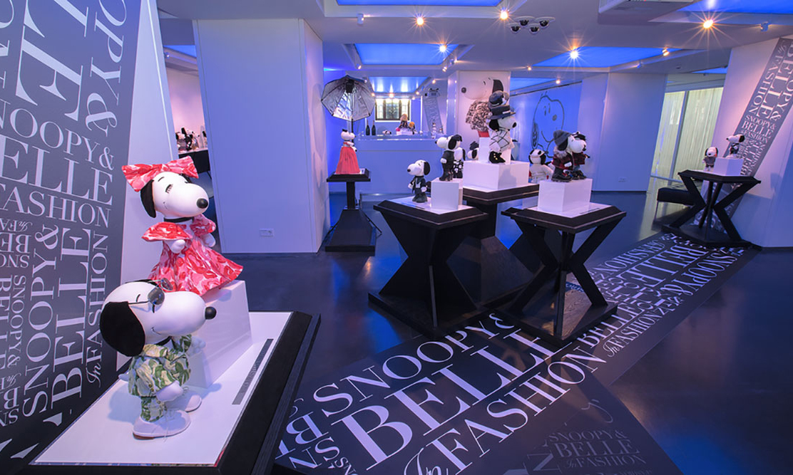 An indoor space with blue lights and several displays of black and white dog statues wearing designer outfits.