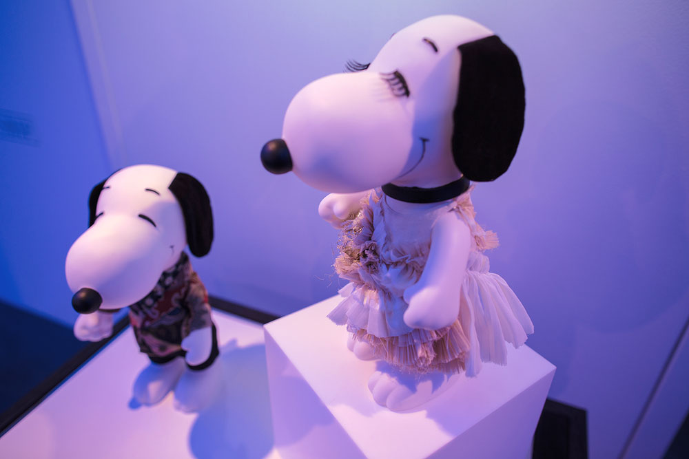 Two black and white dog statues on display in a room with blue lights. One dog is wearing a dress and the other a colourful suit.