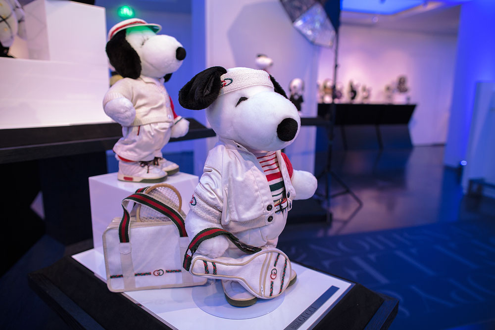 A close-up of two black and white dog statues on display, wearing designer, tennis uniforms.