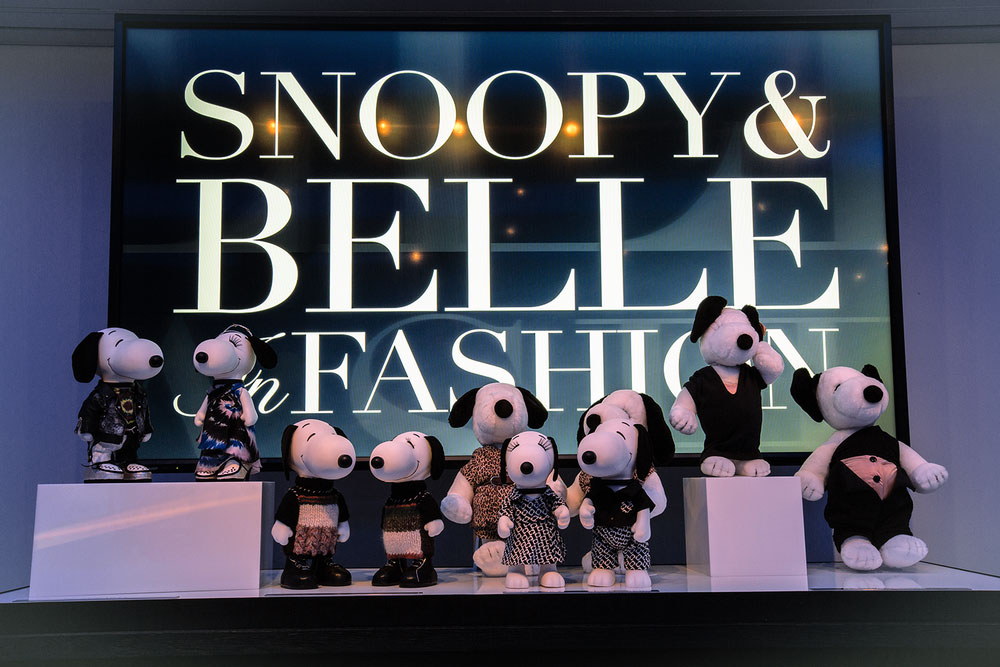 A display of black and white dog statues in front of a large TV screen that reads Snoopy and Belle in Fashion.