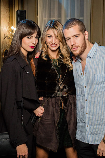 Two women and one man posing for a picture at an event.