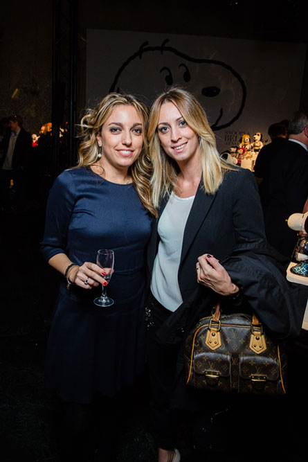 Two blonde woman, dressed in formal attire, standing beside each other posing for a photo at an event.