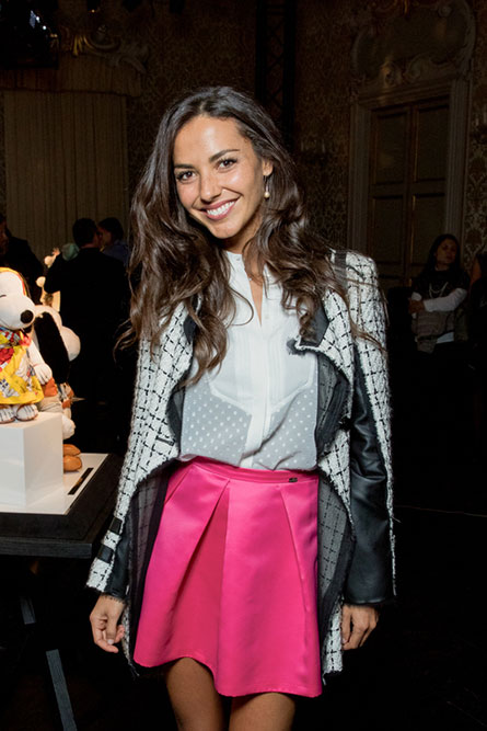 A tall, brunette woman posing for a photo at an event. She is wearing a white blouse, a pink skirt and a grey jacket.